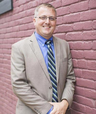 Personal injury, defense, health care, insurance, and litigation attorney Tate Love outside a brick wall